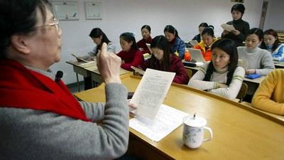 图为一北京学校学生聆听老师上课。(AFP)