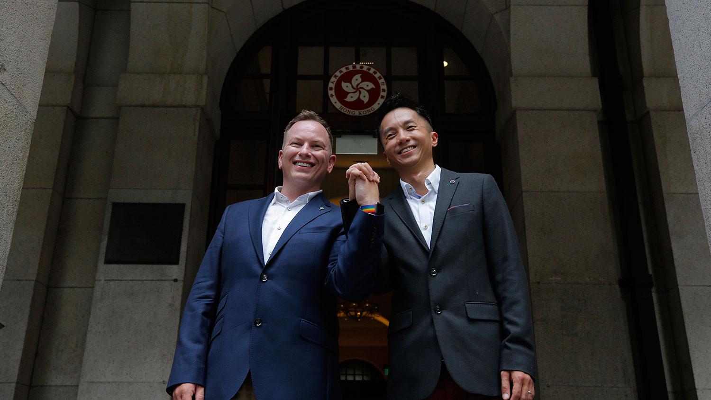 资料图片:2019年6月16日,香港终审法院裁决,同性婚姻伴侣有权获得与异性婚姻伴侣同样的权利和福利。案件涉及2014年在新西兰的香港移民官梁镇罡(Angus Leung)和他的英籍同性婚姻配偶史葛(Scott Adams)。当他们返回香港时,梁镇罡为他的丈夫申请医疗福利但遭到拒绝。这对伴侣还无法申请已婚夫妇的税收优惠。图为香港移民官梁镇罡(左)和他的英籍同性婚姻伴侣史葛携手走在香港终审法院外。(美联社)