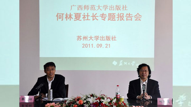 资料图片:2011年9月,时任广西师大出版社社长的何林夏(右)在苏州大学演讲。(苏州大学)