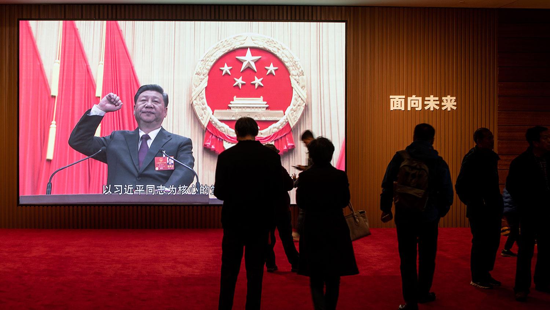 游客在北京中国国家博物馆展览上看到以习近平为核心的图片。(法新社)