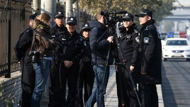图为在北京第三中级法院外的外国记者遭当局人员赶走。 (AFP)
