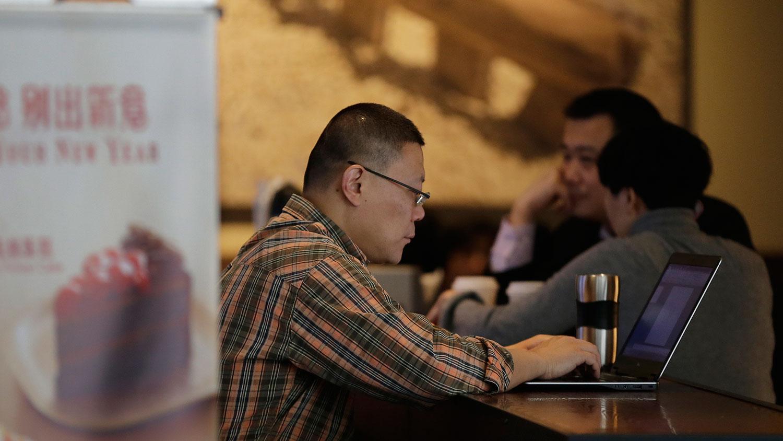 如今网络平台成了民众唯一发声工具,但这一领域不断被中国当局压缩。图为一名男子在北京星巴克咖啡厅,用笔记本上网。(美联社)