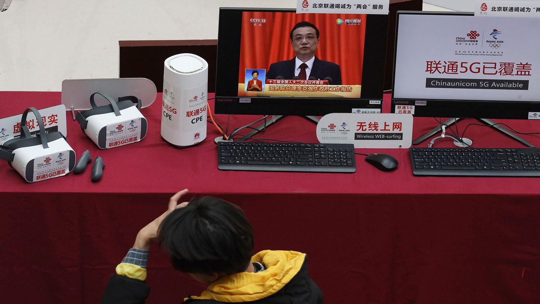 图为,2019年3月6日,中国北京媒体中心展示中国5G技术的演示期间,在监视器上显示中国国务院总理李克强发表工作报告。(美联社)
