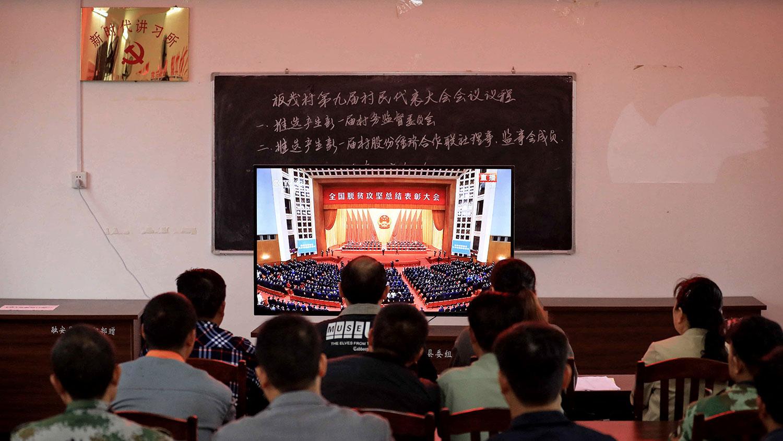 2021年2月25日,新时代讲习所人员观看中国全国脱贫攻坚总结表彰大会。(法新社)