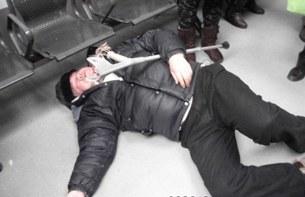 图片:王扣玛被殴打后倒地抽搐,昏迷不醒。(参与网)