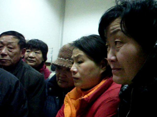 图片:毛恒凤、石萍等人守护着病危中的王扣玛。(参与网)