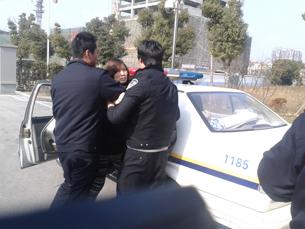 图片:星期二,无锡拆迁户到法院立案途中,被穿警察制服男子带走。(沈军摄/记者乔龙)