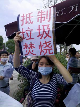 图片:抗议者戴口罩,举标语。(中国茉莉花革命网站)