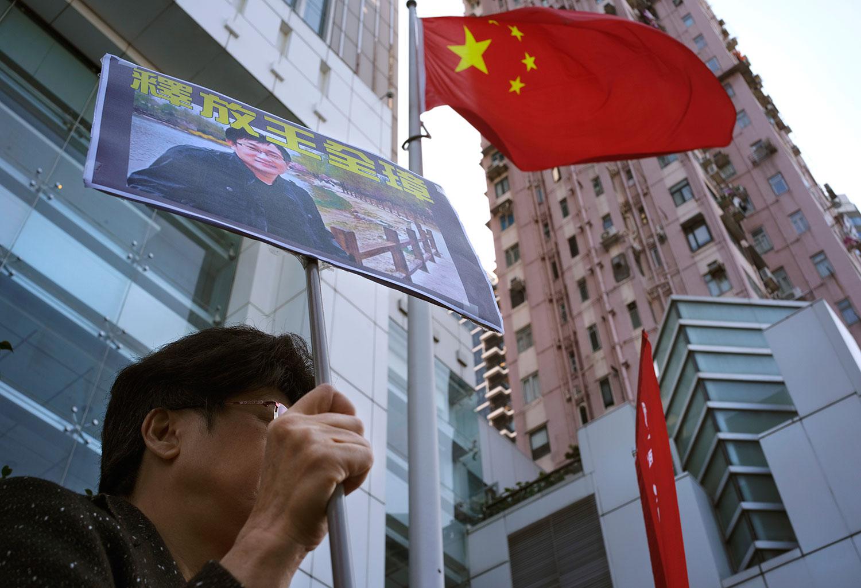 """资料图片:2019年1月29日,中联办外一名示威者拿着""""释放王全璋""""标语牌。(美联社)"""