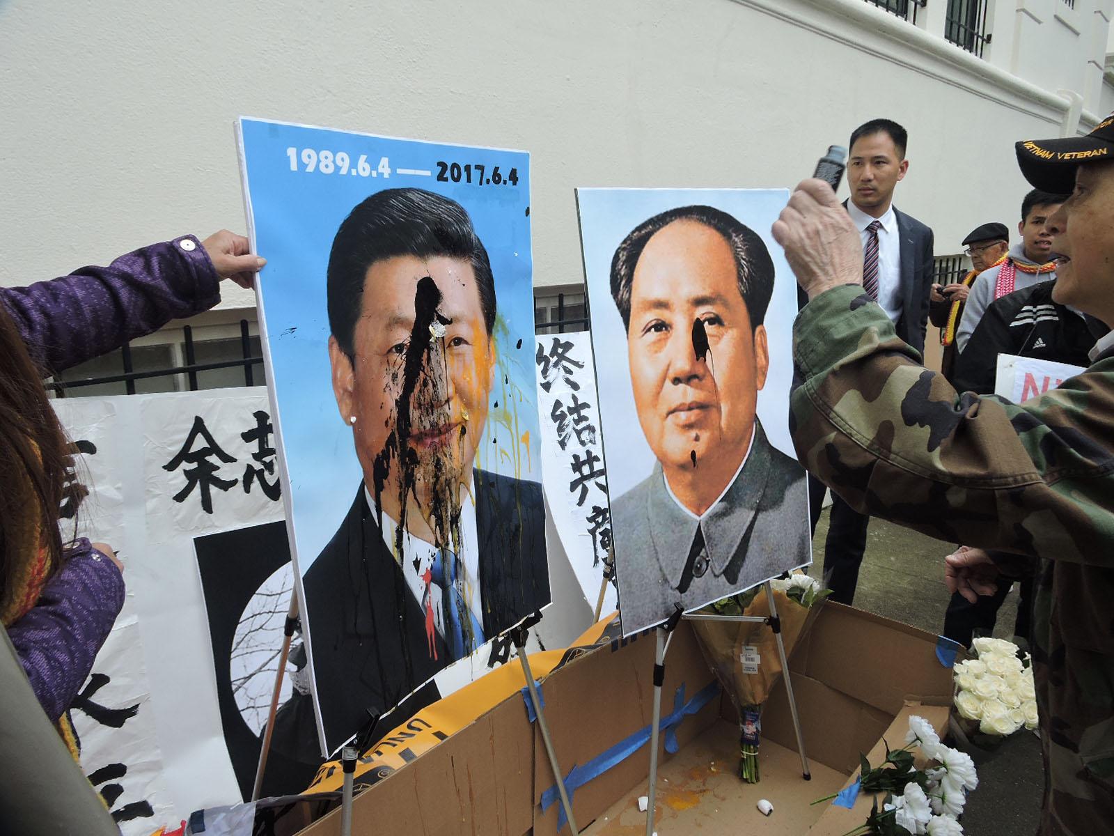 在中领馆前参加悼念余志坚活动的旧金山华人把鸡蛋和颜料掷向毛泽东习近平像(CK摄)