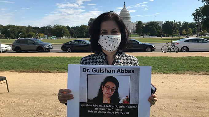 美国维吾尔活动人士罗珊•阿巴斯(Rushan Abbas)手持失踪姐妹的照片(视频截图)