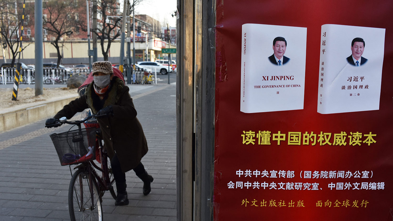 2018年1月19日,北京市一名妇女骑车经过海报,宣传有关习近平的书。 (法新社)