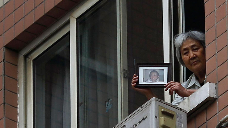 图为,2014年4月24日,张先玲在北京向记者展示她儿子王楠的照片。(路透社)