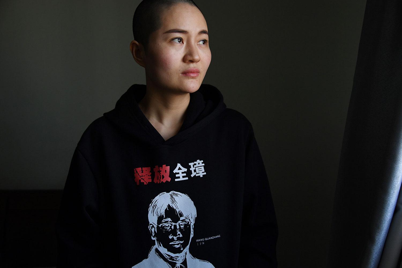 """资料图片:2019年1月28日,中国人权律师王全璋的妻子李文足在北京的家中,穿着一件带有丈夫肖像的衣服,印有""""释放全璋""""的字样。(AFP)"""