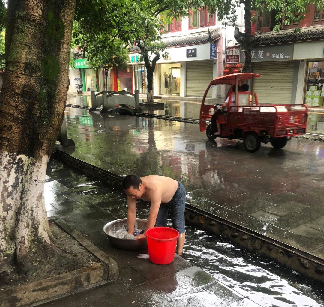 房子遭停水停电,陈云飞要用街上沟里的水洗衣服。(推特图片,拍摄日期不详)
