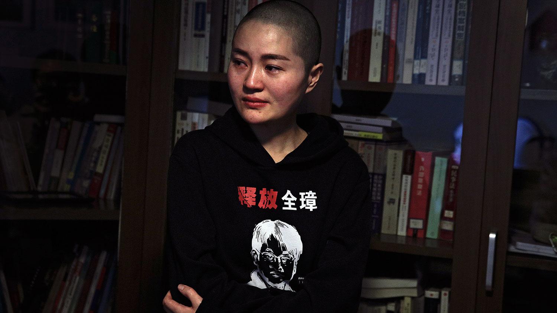 """资料图片:2019年1月28日,中国人权律师王全璋的妻子李文足在北京的家中,穿着一件带有丈夫肖像的衣服,印有""""释放全璋""""的字样。(AP)"""