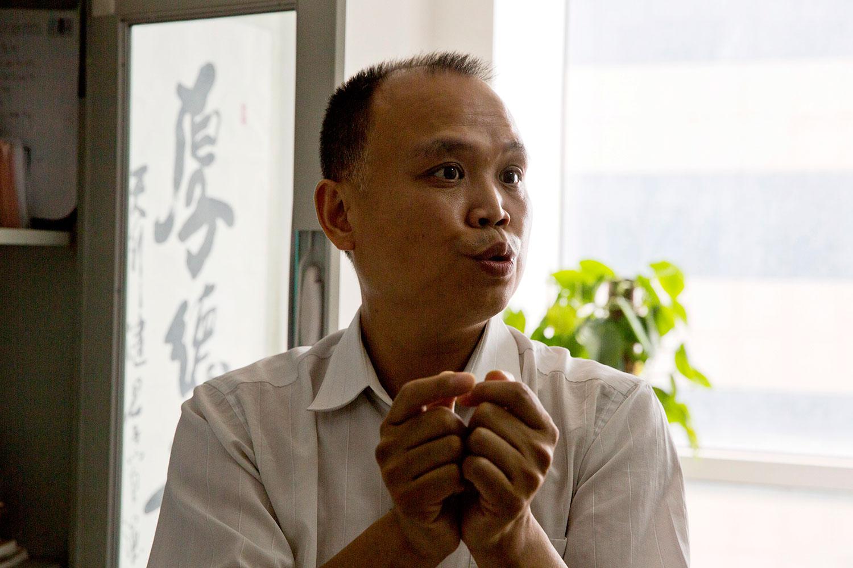 资料图片:2015年7月23日,中国维权律师余文生在北京办公室接受采访时,举起双手展示死刑犯如何一天24小时被铐起来。(美联社)