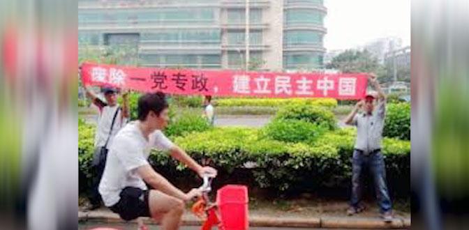 资料图片:2013年9月30日,南方街头运动的推动者陈剑雄和谢文飞走上街头拉横幅宣扬民主,要求废除一党专政,建立民主中国。(维权网)
