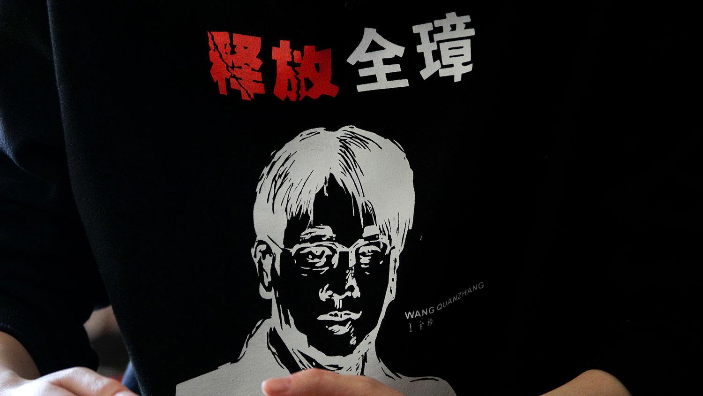 """2019年1月28日,中国人权律师王全璋的妻子李文足在北京的家中,穿着一件带有丈夫肖像的毛衣,印有""""释放全璋""""的字样。(AP)"""