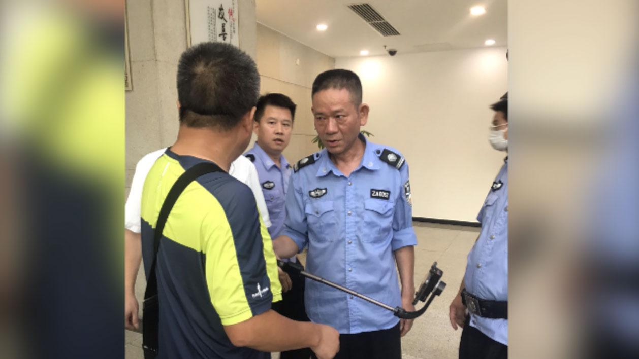 2020年9月11日,长沙中院法警阻止谢阳拍摄。(施明磊推特)
