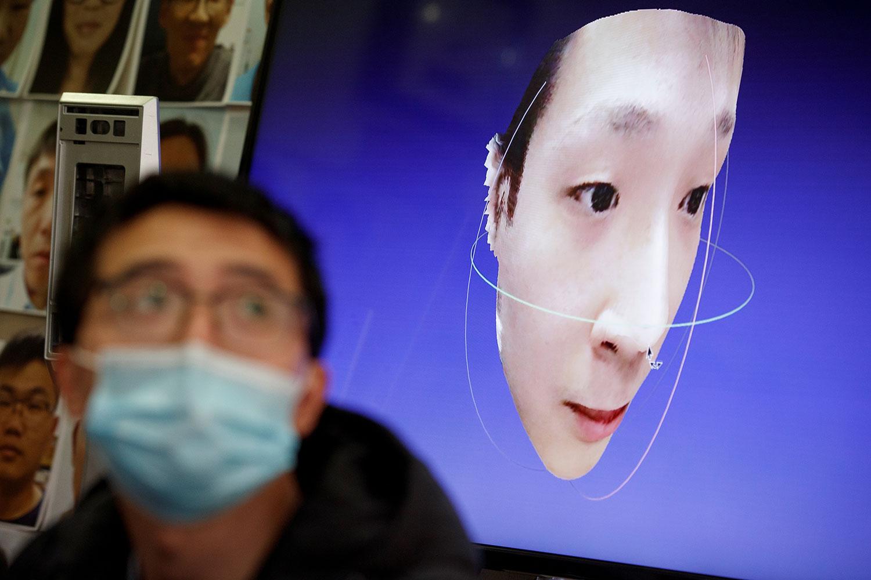 资料图片:2020年3月6日,北京汉王科技的工程师正在研发可以识别戴着口罩的人的人脸识别技术。(路透社)