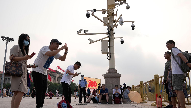 2021 年 7 月 15 日,在北京天安门广场附近,人们在监视摄像机附近拍照。(美联社)