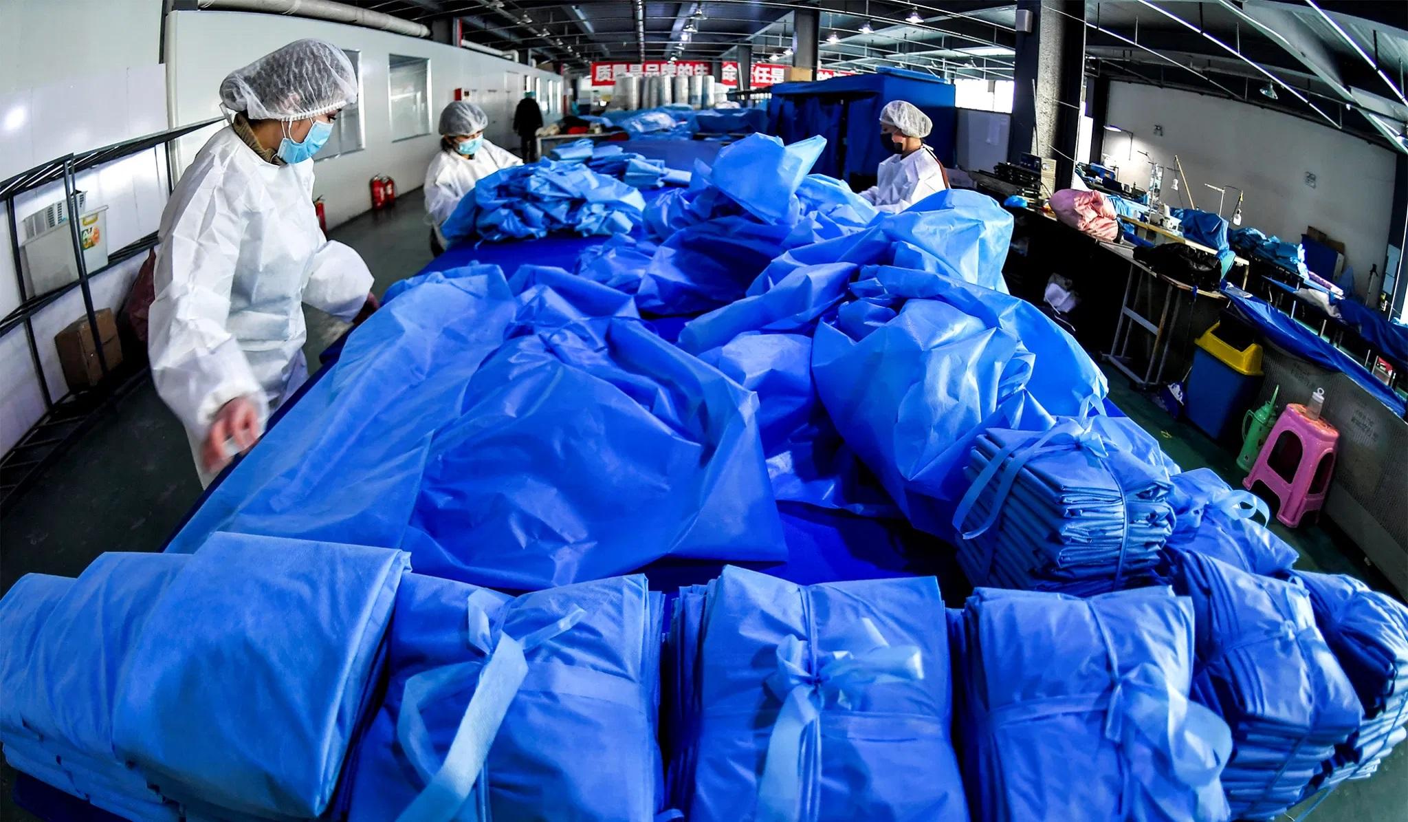 资料图片:2020年1月27日,在中国新疆维吾尔自治区乌鲁木齐市一家医疗设备制造商的工厂里,工人在生产防护服和口罩的生产线上劳动。(路透社)