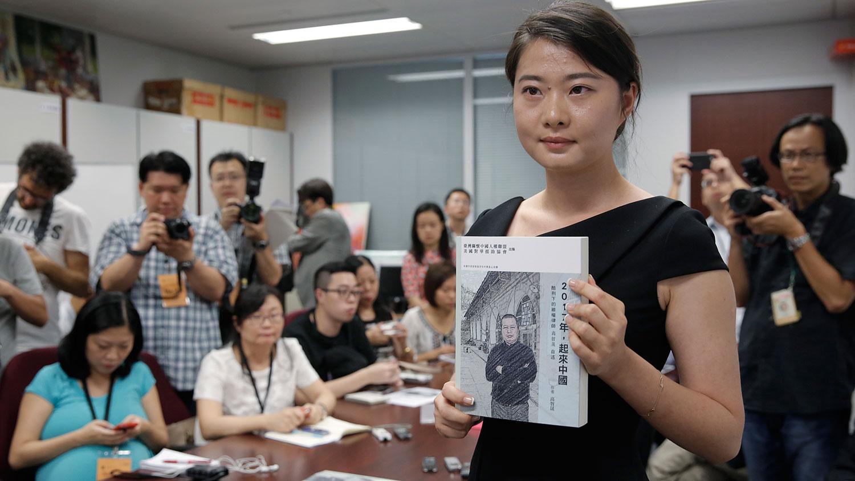 2016年6月14日,中国维权律师高智晟的女儿耿格在香港展示父亲的书《2017年,起来中国》。(美联社)