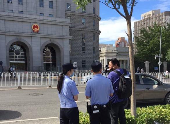 被拒采访的外媒记者在法院对开马路边拍摄,亦遭警察盘查。(小健拍摄/记者乔龙)