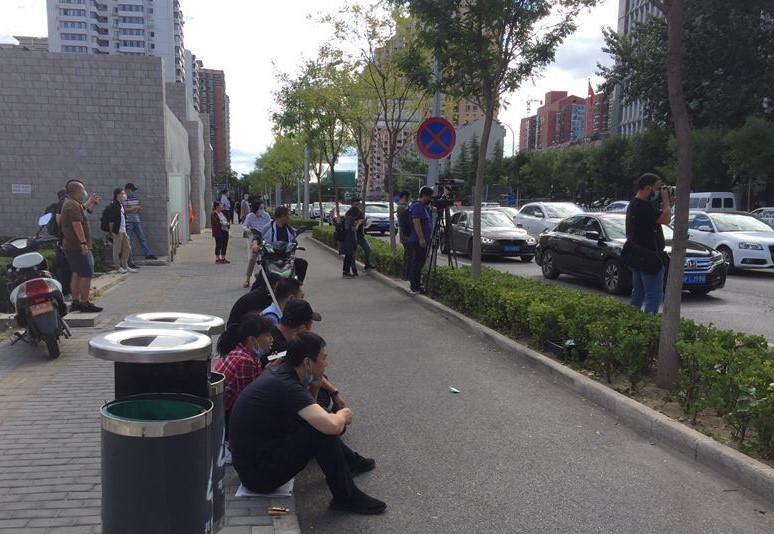 有民众坐在法院对开路边,等候法庭消息。(推特图片/乔龙提供)