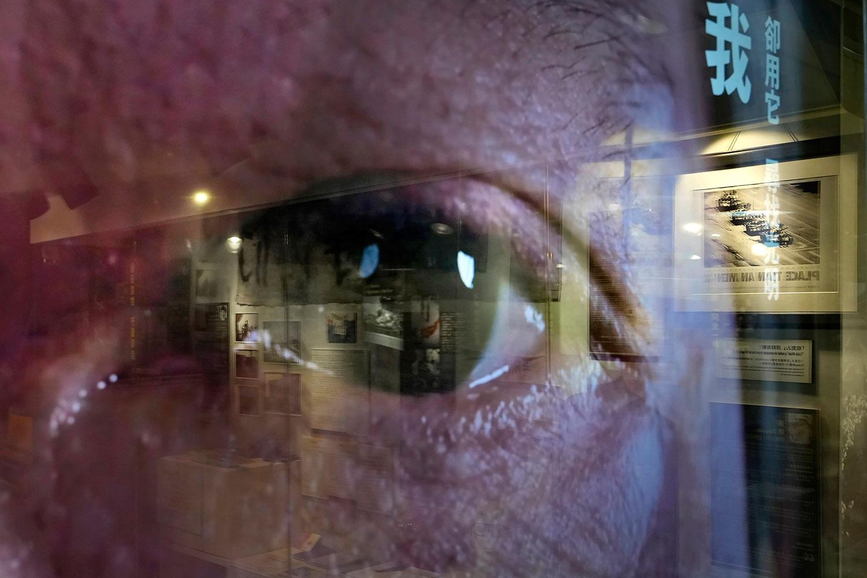 """资料图片:一名民众的眼睛出现在电视屏幕上,一幅幅描绘 1989 年北京民主运动中图片在香港""""六四纪念馆""""展出。(美联社) ."""