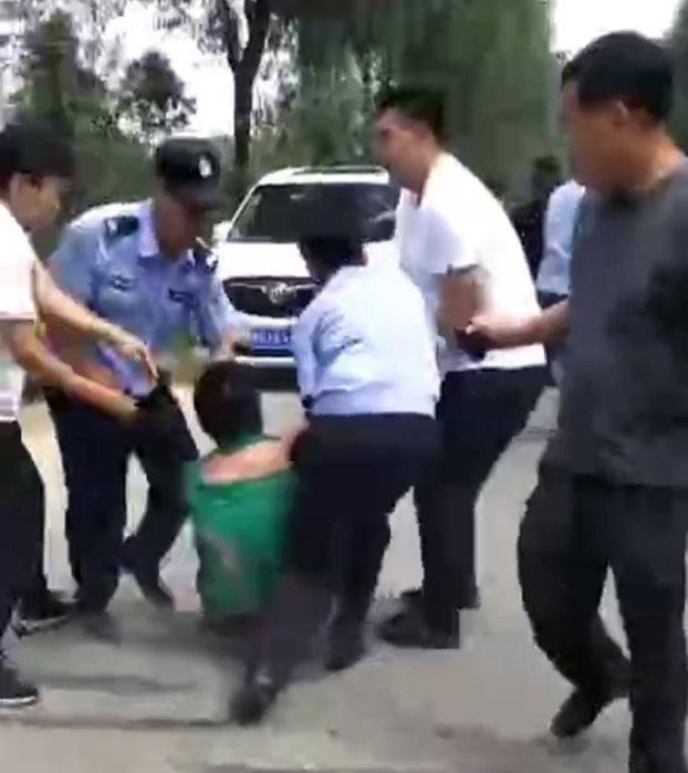 一名示威者被多名公安抬走。(视频截图)