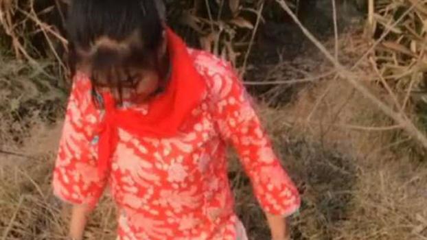 四川省仁寿县一女子戴红领巾捕鱼视频热传,当事人遭刑事拘留。(视频截图)