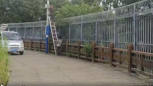 云南畹町在中缅边境中方境内的云南畹町,工程人员为新建的围墙按装监控镜头。(视频截图)