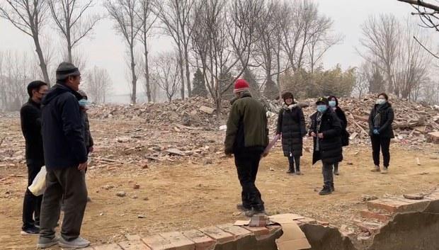 2021年2月13日,宗同昌(戴红帽者)在袁氏三礼故居废墟前。(photo:RFA)