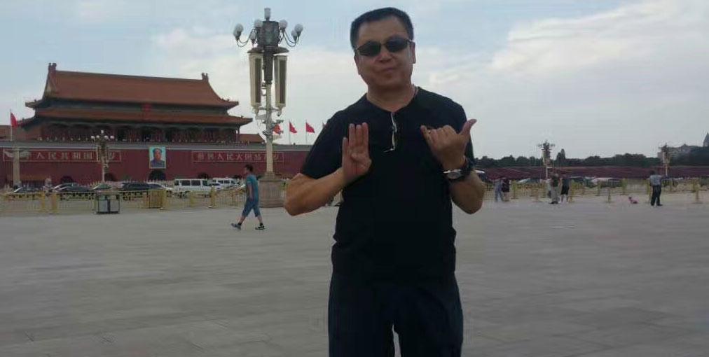 """新公民运动成员张宝成在天安门广场手比出""""六""""和""""四""""手势的照片。(张宝成提供)"""