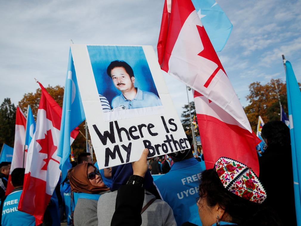 资料图片:2018年11月6日,一名维吾尔族人士举牌参加抗议活动,牌子上写着:我的兄弟在哪里(Where is my brother)。(图/路透社)