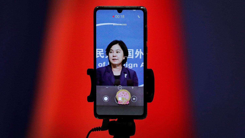 图为,一部智能手机画面显示,中国外交部发言人华春莹在例行记者会上。(美联社)