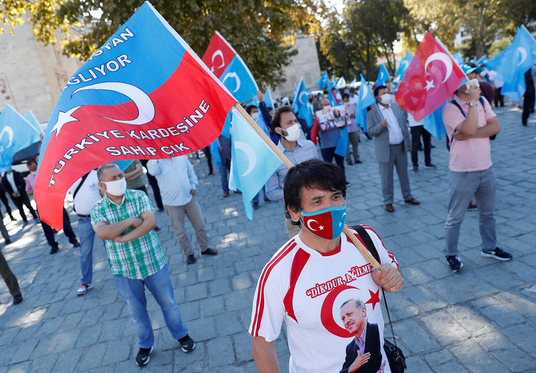 2020年10月1日,维吾尔族示威者在土耳其伊斯坦布尔抗议中国新疆政策,一示威者穿着印有土耳其总统埃尔多安照片的T恤衫。(路透社)
