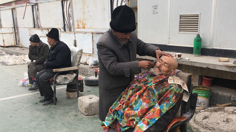 """中国新疆维吾尔自治区政府发布的遏制极端主义的条例中包括:禁止男子留""""不正常""""的胡须,禁止妇女在公共场合穿戴掩盖全身的罩袍,或遮盖脸面的面纱。图为,2018年2月18日,一名理发师在新疆地区喀什一清真寺外刮胡子。(法新社)"""