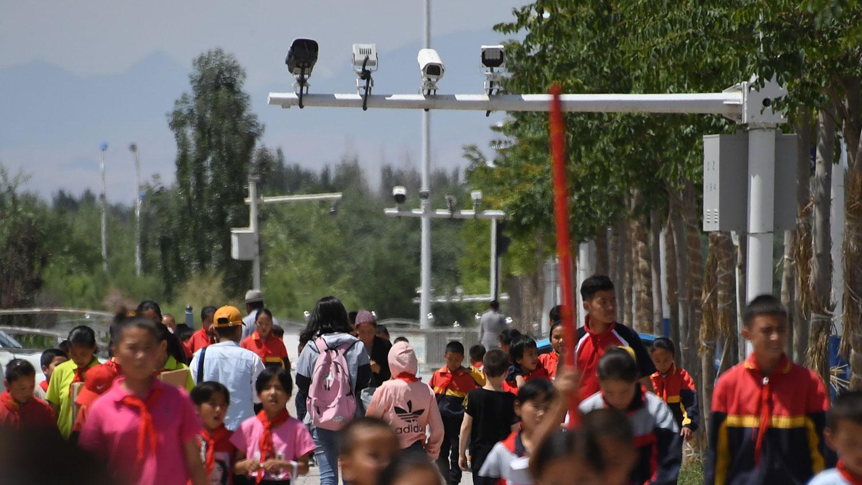 文件又透露了当局监视维吾尔人的方式,包括利用脸部辨识的监视器、派出干部驻守清真寺和进行家庭访问等。图为,2019年6月4日,学童在新疆地区喀的监视摄像机下行走。(法新社)