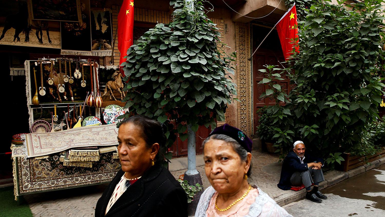 外界担心,新法实施后,政府组织介入新疆少数民族家庭生活的情况,会变本加厉。图为,新疆维吾尔自治区喀什古城墙插着中国国旗。(路透社资料图片)
