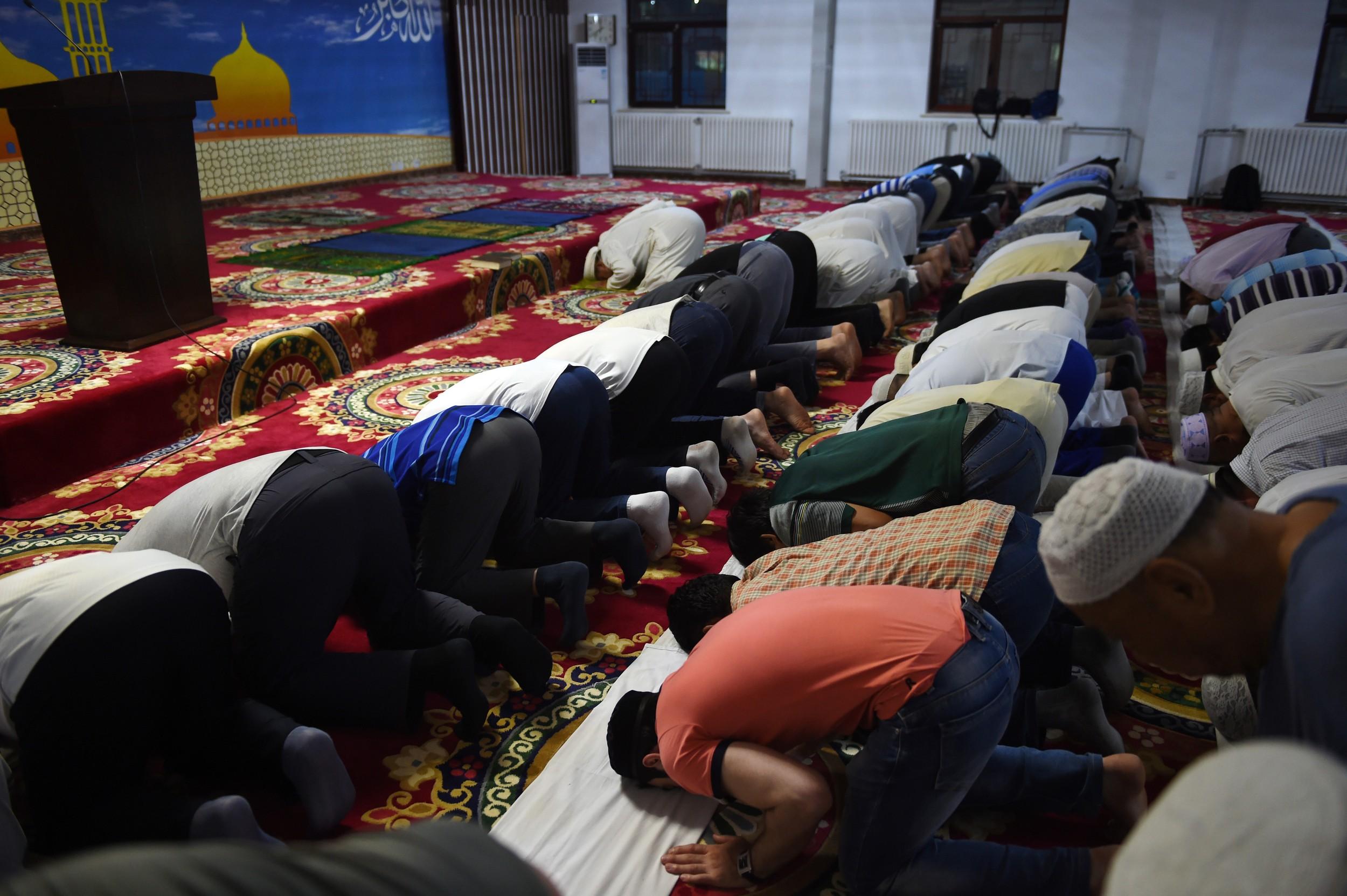图为,2015年6月18日,穆斯林斋月的第一天,在北京的穆斯林们在一个清真寺内祷告。(法新社)