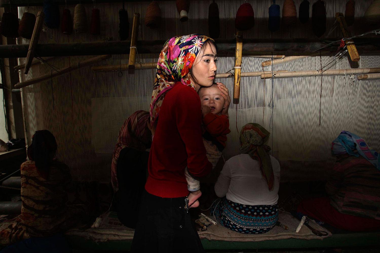 资料图片:中国和田市的一家地毯工厂里,一名维吾尔族妇女在地毯织布休息时照顾她的孩子。(AP)