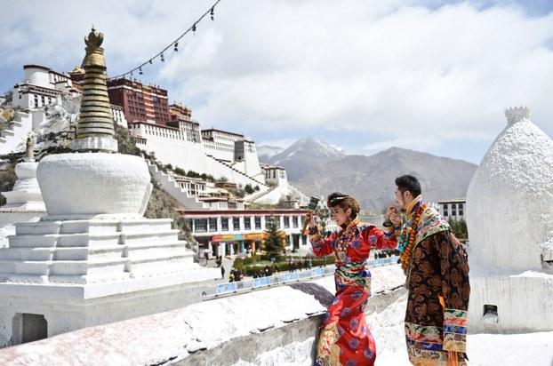 一對新人身穿傳統藏服,在拉薩布達拉宮前拍攝結婚照。 (法新社資料圖片)