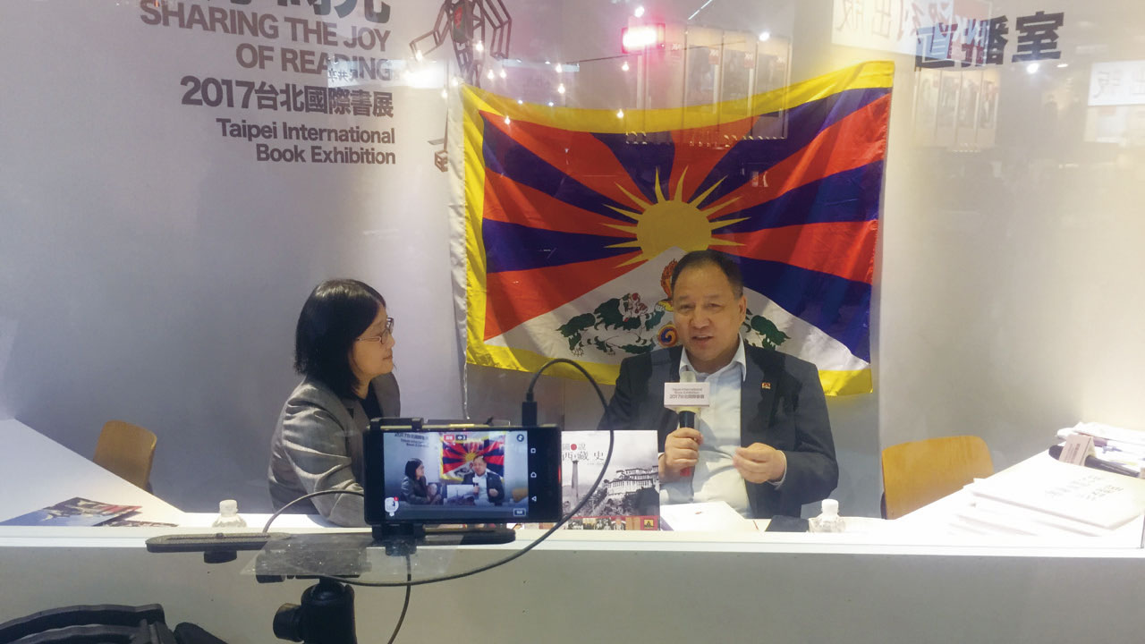 达瓦才仁在台北国际书展,与雪域出版社主编卢惠娟向社会大众解说西藏。(达赖喇嘛西藏宗教基金会提供)