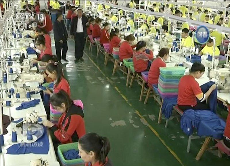 图为中国央视播出画面,穆斯林学员在中国西北部和田市和田职业教育培训中心的一家制衣厂工作。 (AP视频图)
