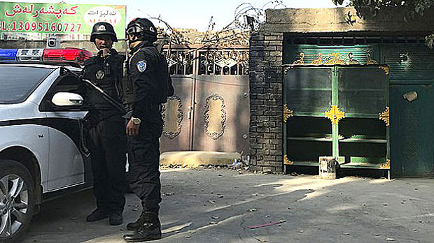 """在新疆一所""""再教育营""""外巡逻的警察(美联社)"""