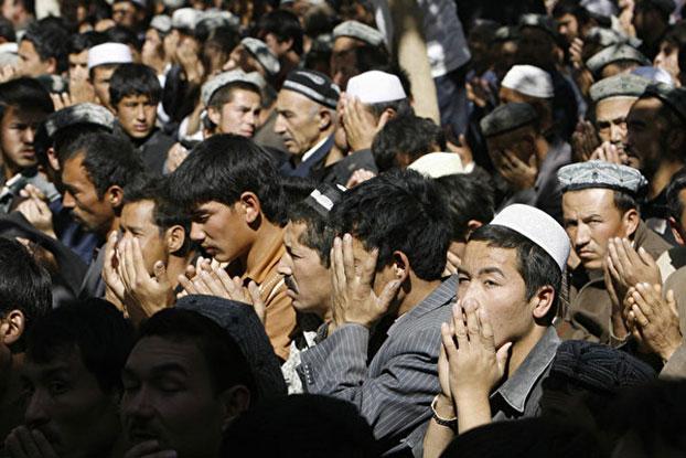 """新疆民族村大部分男性被关进""""再教育营"""",与监狱无异。图为2006年10月13日,新疆维吾尔族人在斋戒月进行祈祷。(AFP)"""