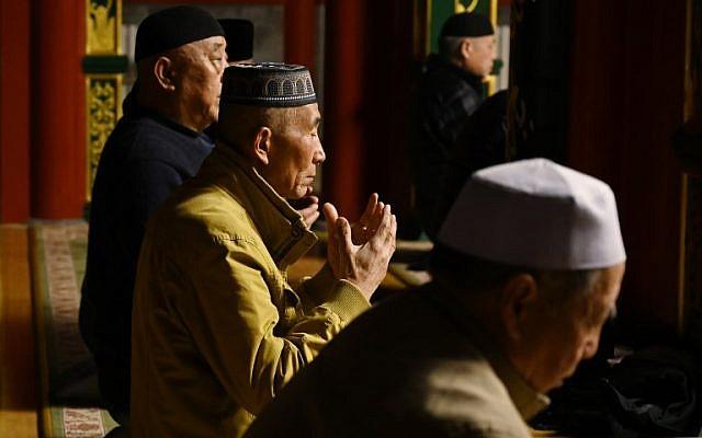 资料图片:2019年3月18日,维吾尔穆斯林男子在北京的一座清真寺祈祷。(法新社)
